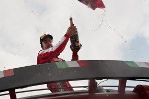 pilota sul podio festeggia la vittoria